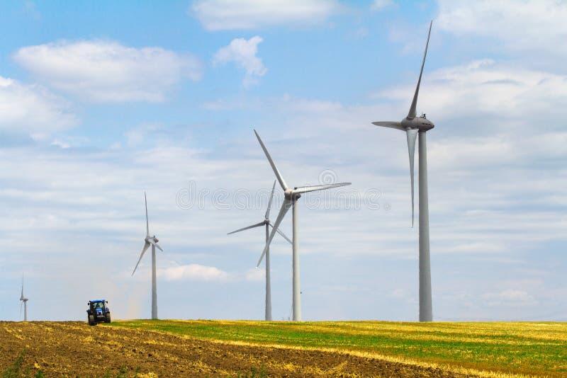 Eolian Windkraftanlage mit Pflugtraktor im Hintergrund lizenzfreie stockbilder