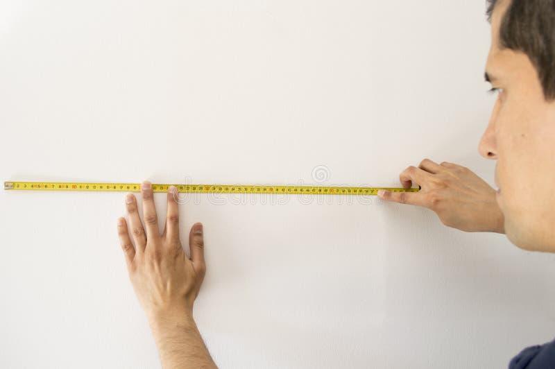 Eople που δείχνει σε μια μετρώντας ταινία στον τοίχο στοκ εικόνα