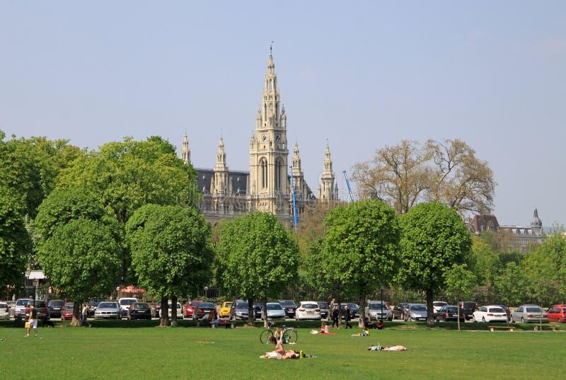 Eople ослабляя в парке в вене около дворца Hofburg имперского с здание муниципалитетом вены на заднем плане стоковые изображения