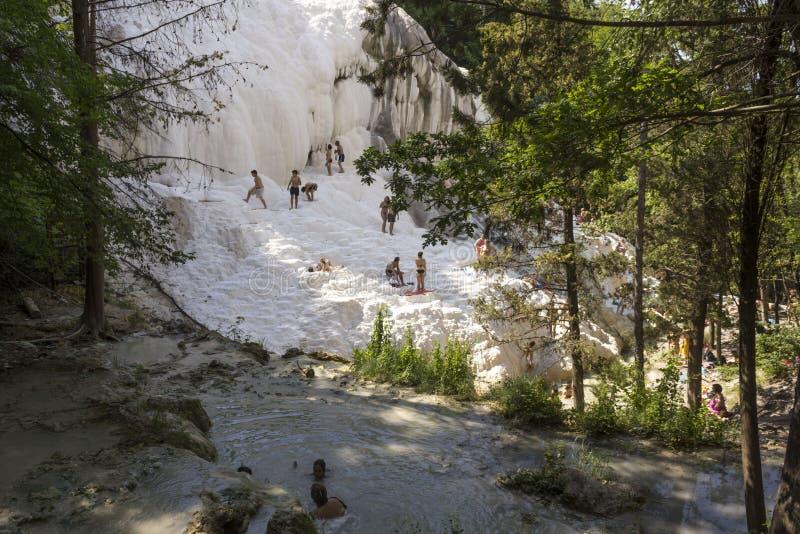 Eople que se baña en las piscinas termales naturales de Bagni San Filippo en Toscana, Italia imágenes de archivo libres de regalías