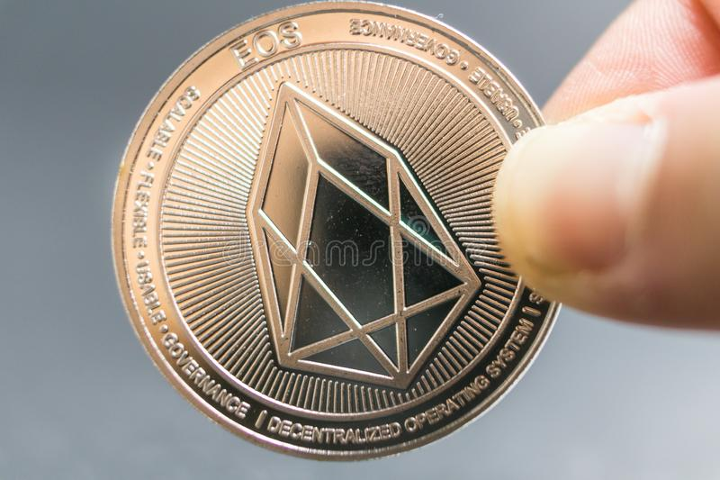 EOS, Crypto waluty srebna moneta, Makro- strzał odizolowywający na tle joty moneta, ciie za Blockchain technologii, fotografia royalty free