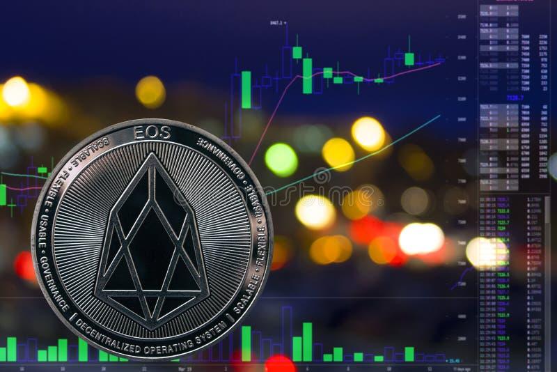 EOS de cryptocurrency de pièce de monnaie sur le fond et le diagramme de ville de nuit images stock