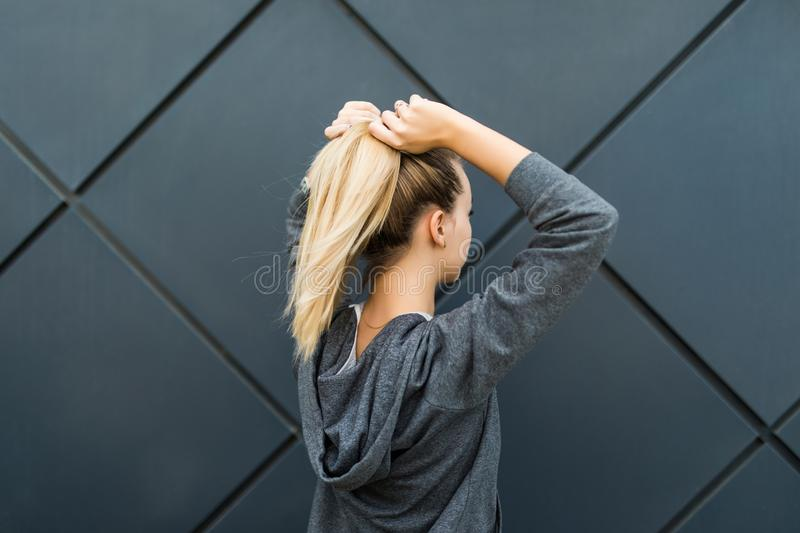 Epic back view of strong fit female athlete getting ready for workout towards the sun. Strong fitness woman tying ponytail. Motiva stock images