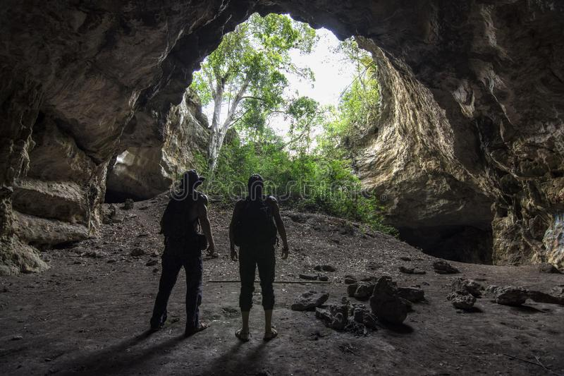 Epic cave adventure in Chiapas, Mexico. Silhouette of two male explorers standing at bottom of circular cave opening in jungle of Chiapas, Mexico royalty free stock photos