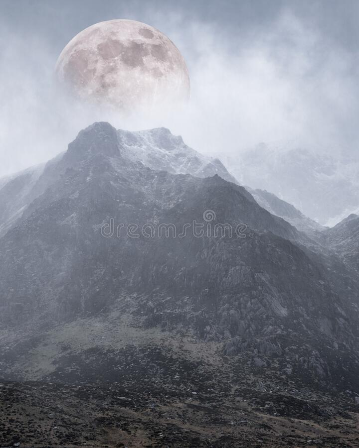 Epic digital composite image of Supermoon above mountain range giving very surreal fantasy look to the dramatic landscape image royalty free stock images