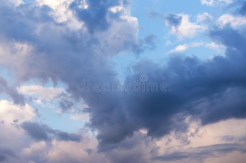 Epic dramatic storm cumulus fluffy clouds in sunlight against blue sky background, heaven texture. Epic dramatic beautiful storm cumulus fluffy clouds in royalty free stock photos