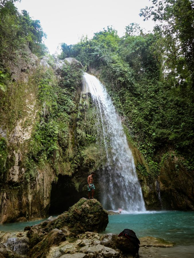 Man alone in deep forest waterfall, inambakan falls in Cebu Island in Philppines. Epic man alone in deep forest waterfall from mountain gorge at hidden tropical stock photography