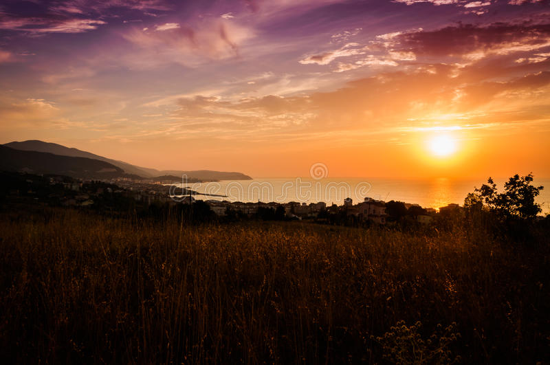 Epic Pastoral Seascape Sunset. Beautiful and epic cloudy sunset on a gorgeous pastoral land and seascape with mountains, capes and islands royalty free stock image