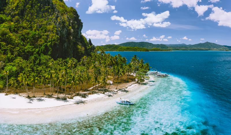 Epic Pinagbuyutan Island, El Nido, Palawan, Philippines. Aerial drone view of remote secluded tropical white sandy beach. With coconut palm trees and turquoise royalty free stock photo