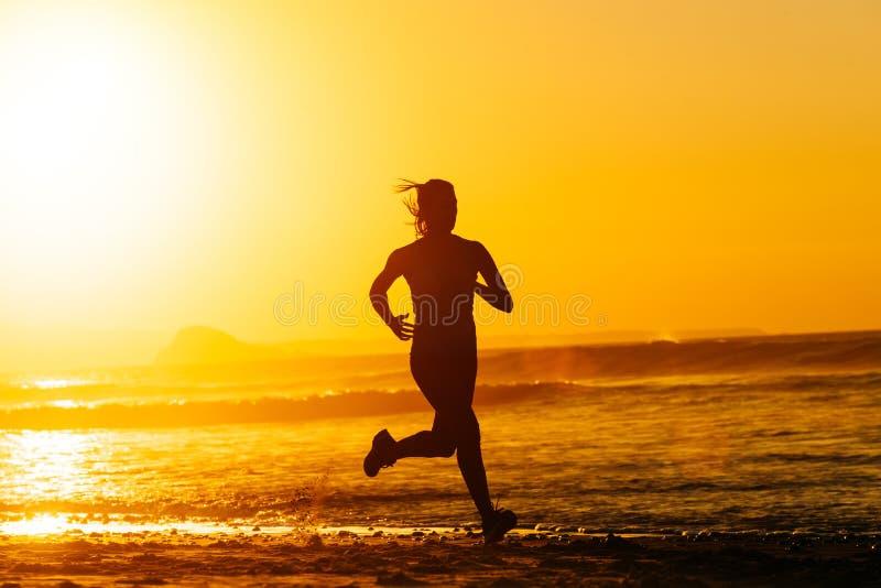 Epic runner training on summer sunset stock photography