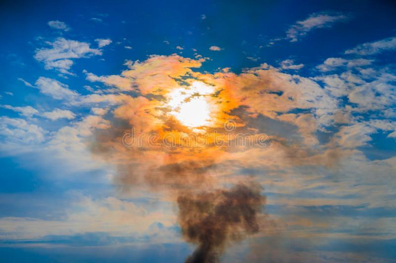 Epic sky landscape, with white blue and white clouds, shining orange sun and smoke from a fire stock photography