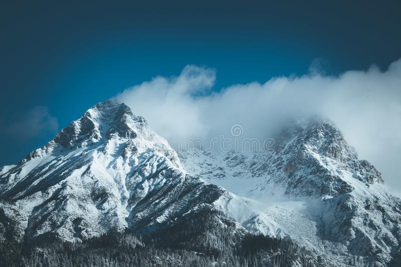 Epic snowy mountain peak with clouds in winter, landscape, alps, austria. Lpeak cliffy adventure rock misty clear solid stone cliffhanger beautiful scenery stock photography
