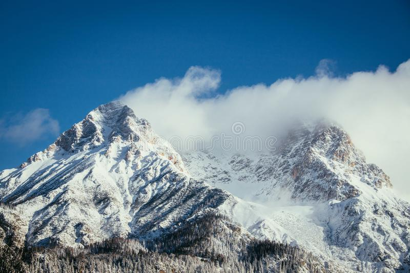 Epic snowy mountain peak with clouds in winter, landscape, alps, austria. Lpeak cliffy adventure rock misty clear solid stone cliffhanger beautiful scenery royalty free stock photography