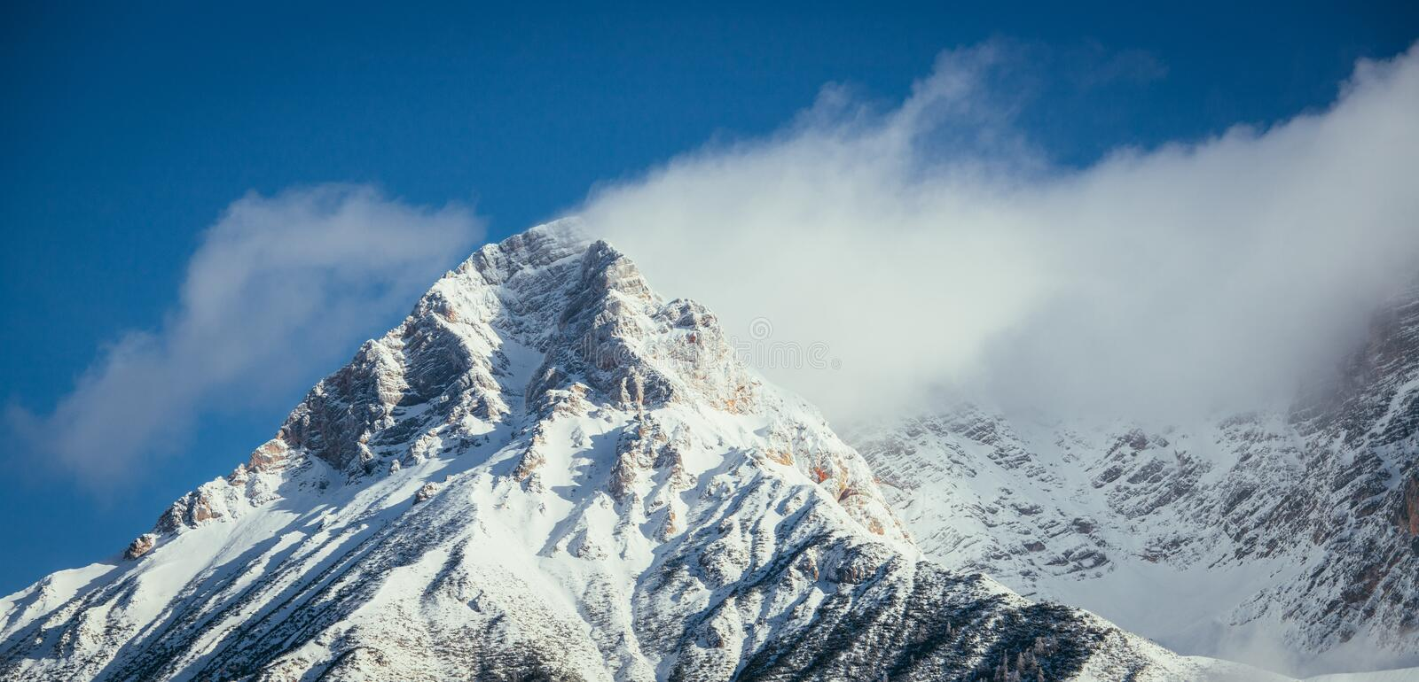Epic snowy mountain peak with clouds in winter, landscape, alps, austria. Lpeak cliffy adventure rock misty clear solid stone cliffhanger beautiful scenery stock image