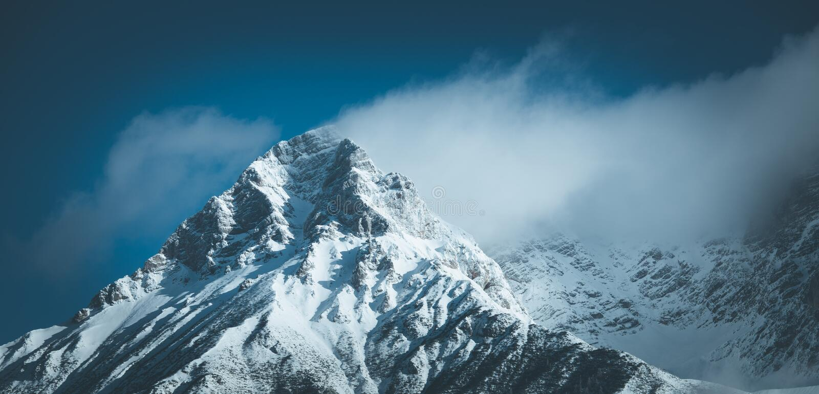 Epic snowy mountain peak with clouds in winter, landscape, alps, austria. Lpeak cliffy adventure rock misty clear solid stone cliffhanger beautiful scenery royalty free stock photos