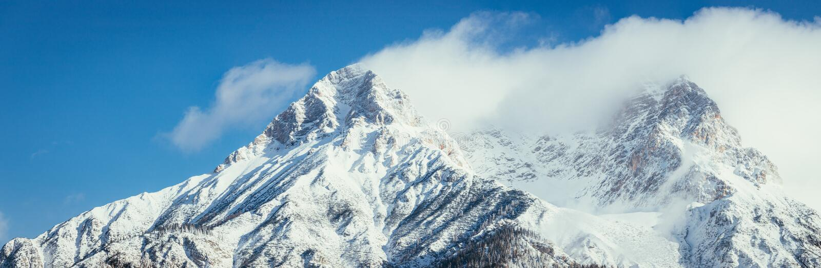 Epic snowy mountain peak with clouds in winter, landscape, alps, austria. Lpeak cliffy adventure rock misty clear solid stone cliffhanger beautiful scenery stock images