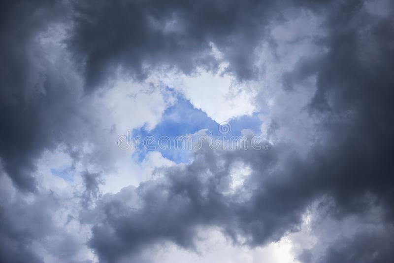 Epic Storm sky, dark clouds background texture. Darkness and light. Cumulus epic scenic storm clouds in the blue sky background texture royalty free stock photos