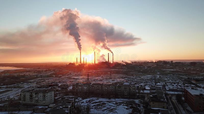 Epic sunset on the background of a Smoking factory. The red sun with bright rays goes beyond the pipe factories and smog. royalty free stock images