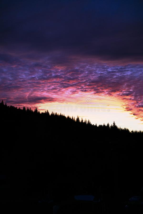 Epic vivid colorful sunset behind the forest in Vsetin, Czech Republic stock photography