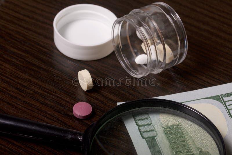 A epidemia das drogas As tabuletas estão em um recipiente plástico claro com a tampa removida Mentira de diversas tabuletas na ta fotos de stock
