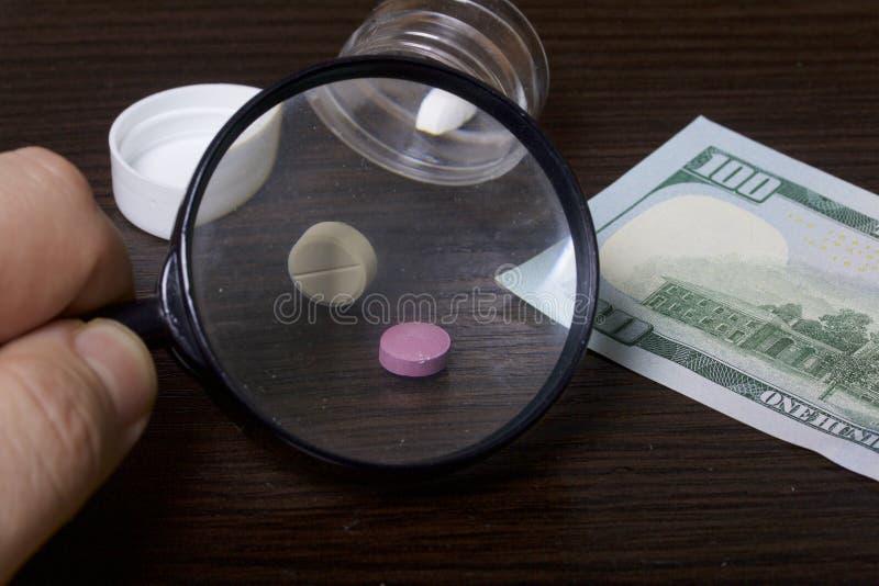 A epidemia das drogas As tabuletas estão em um recipiente plástico claro com a tampa removida Mentira de diversas tabuletas na ta foto de stock royalty free