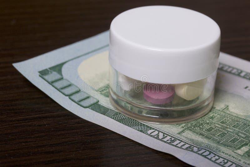 A epidemia das drogas As tabuletas estão em um recipiente plástico transparente Estão em uma conta de dinheiro fotografia de stock royalty free