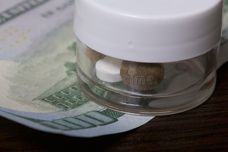 A epidemia das drogas As tabuletas estão em um recipiente plástico transparente Estão em uma conta de dinheiro fotos de stock