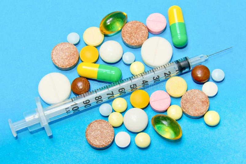 Epidemia de opióides Pílulas opióides Conceito de abuso de drogas - comprimidos e seringa coloridos diferentes sobre fundo azul foto de stock royalty free