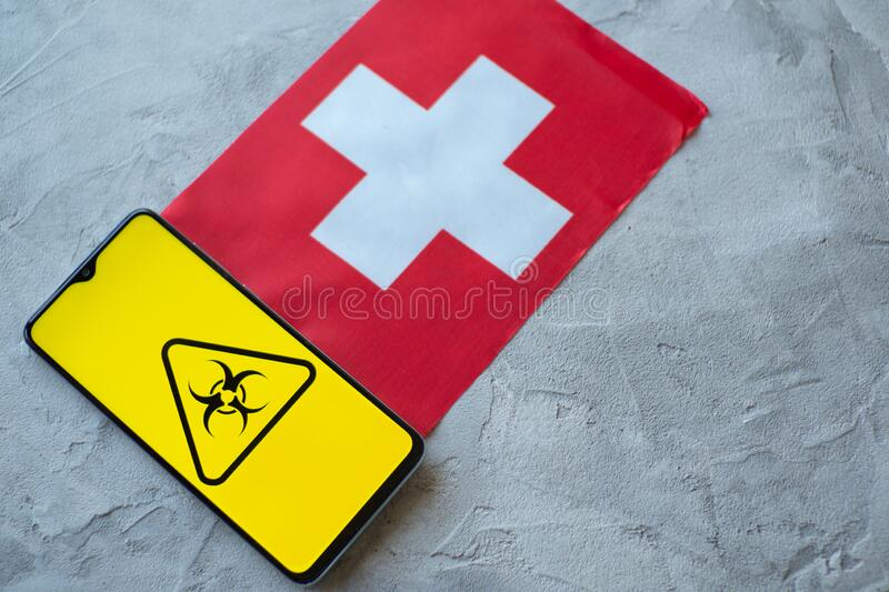 Epidemiological situation in the country Switzerland. Flag and smartphone with news and a biohazard symbol. The pandemic virus, concept royalty free stock photo