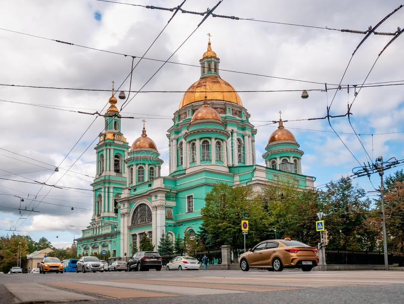 Epiphany Cathedral at Yelokhovo is vicarial church of Moscow Patriarchs. In foreground are taxi cars of most common brand in city royalty free stock image