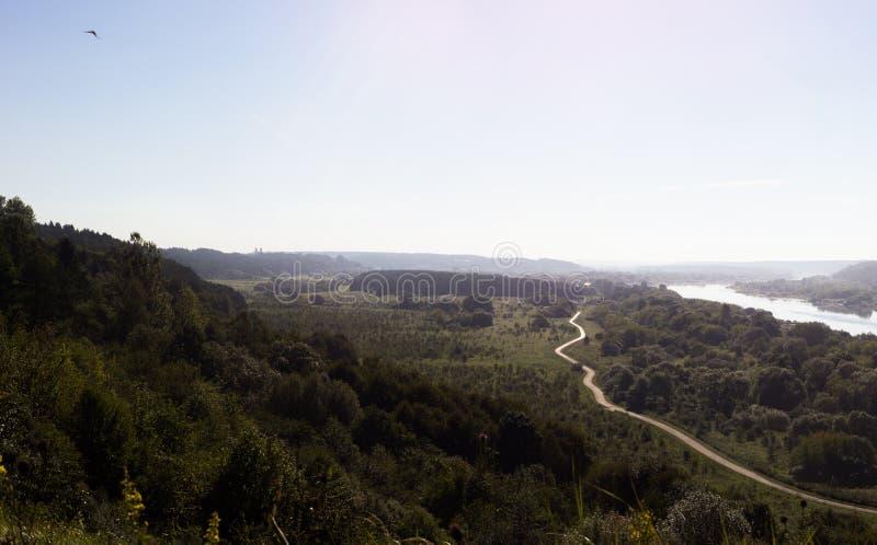 Episch panorama van omhooggaande heuvel met rivier en smalle weg stock foto