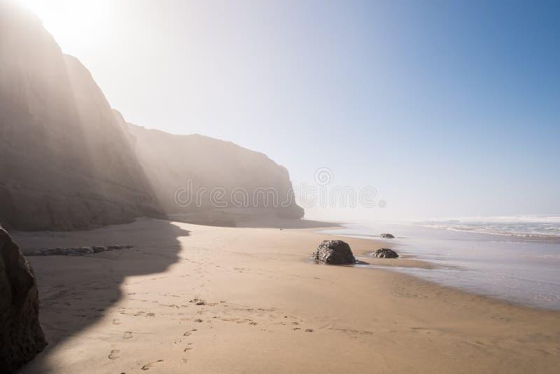 Epische Misty Beach mit Klippen stockfoto