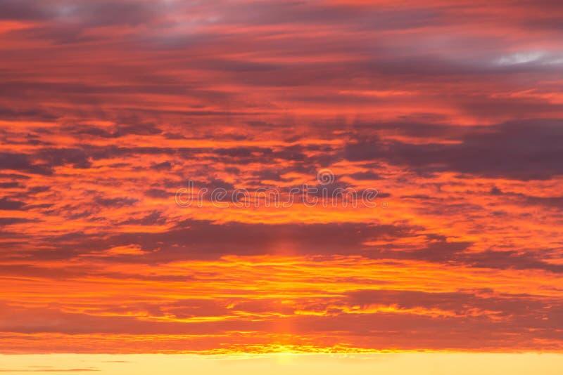 Epischer drastischer Sonnenuntergang, orange Himmel des Sonnenaufgangs mit Wolken und Sonnenlichthintergrund stockfoto