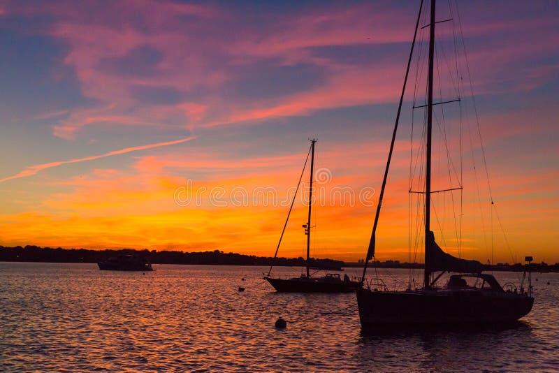 Episk och härlig solnedgång över hamn med segelbåtsilouettes royaltyfri bild