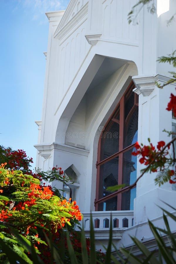 Episkopalkyrkan för St Paul ` s med det ljusa orange blomningträdet på en sommardag i Key West, Florida arkivfoton