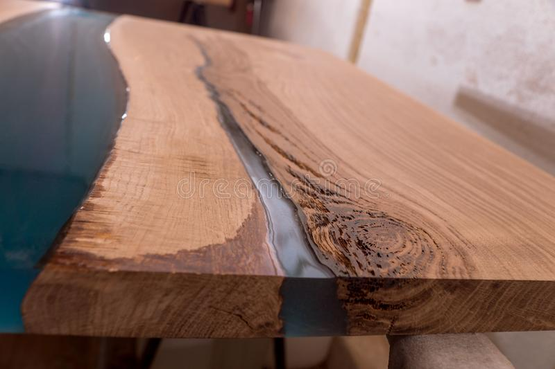 Epoxy resin in cracked walnut massif. Artistic processing of wood. furniture loft. modern furnishings. table-tops. stock photography