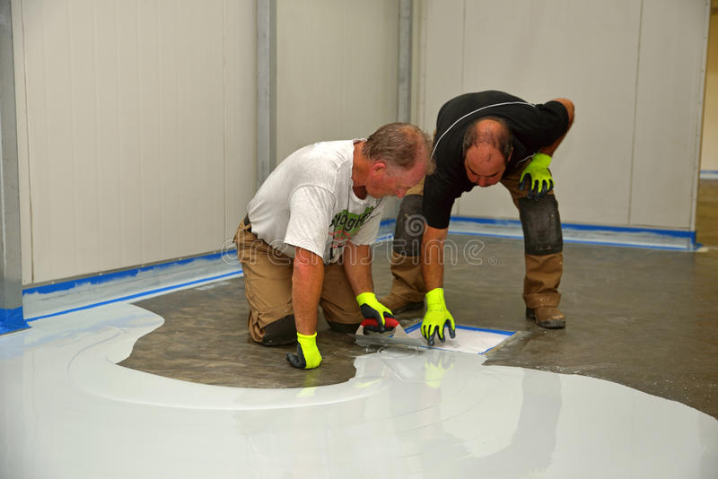 Epoxy surface for floor. Tradesmen check the quality of an epoxy product applied to the floor of an industrial building royalty free stock image