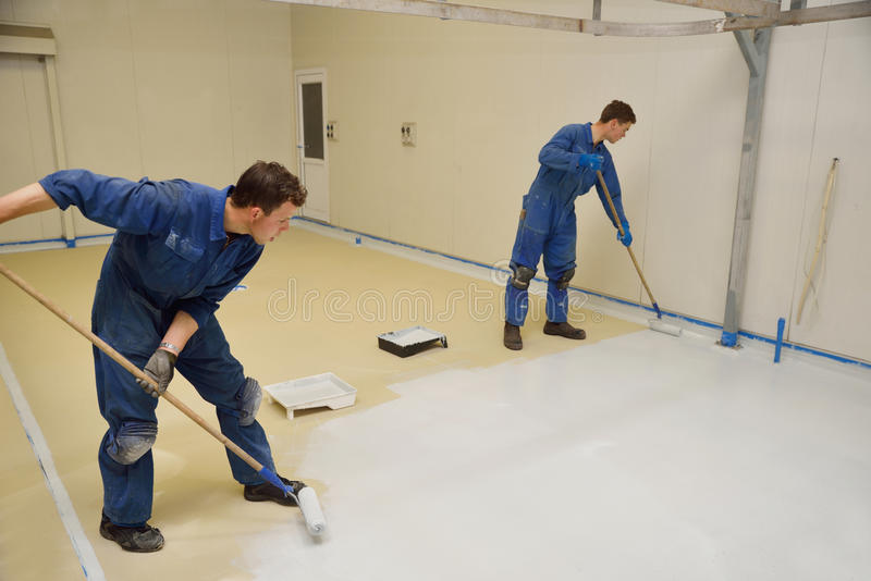 Epoxy surface for floor. Tradesmen rolling final coat of epoxy product on the floor of an industrial building royalty free stock photography