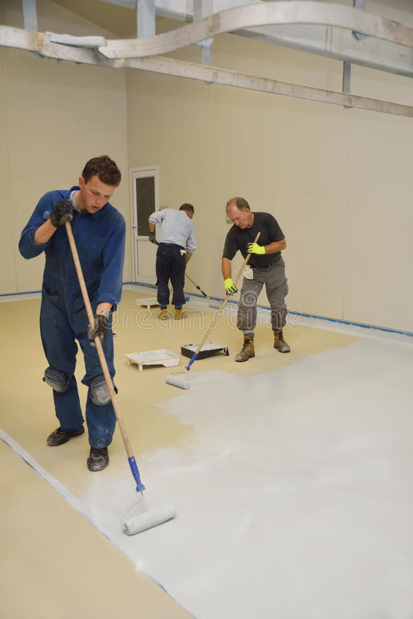 Epoxy surface for floor. Tradesmen rolling final coat of epoxy product on the floor of an industrial building stock images