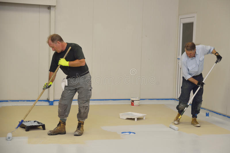 Epoxy surface for floor. Tradesmen rolling final coat of epoxy product on the floor of an industrial building royalty free stock photo