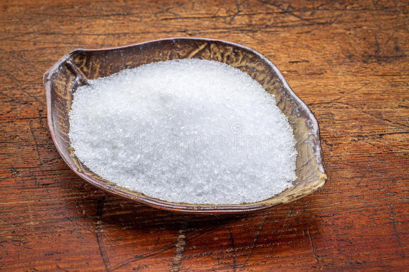 Epsom salts (Magnesium sulfate ). Epsom salts (Magnesium sulfate) in a leaf shaped ceramic bowl against rustic wood - relaxing bath concept royalty free stock image
