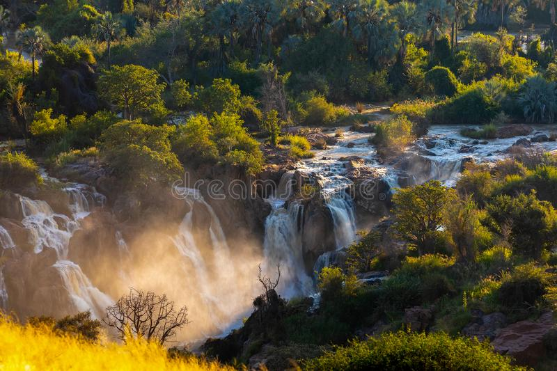 Epupa Falls on the Kunene River in Namibia. Epupa Falls on the Kunene River in Northern Namibia and Southern Angola border. Sunrise sunlight in water mist stock photography