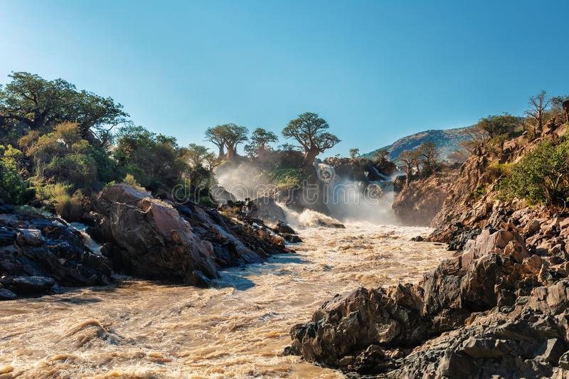 Epupa Falls on the Kunene River in Namibia. Famous Epupa Falls on the Kunene River in Northern Namibia and Southern Angola border. Sunrise sunlight in water mist stock images