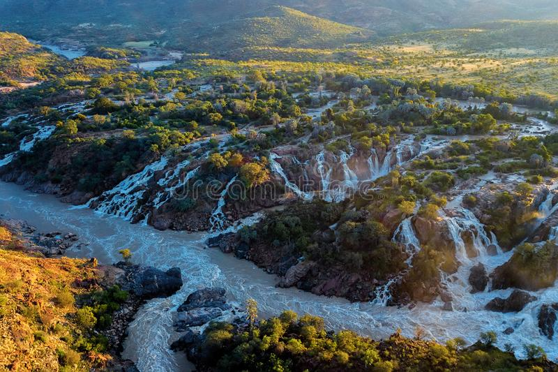 Epupa Falls on the Kunene River in Namibia. Famous Epupa Falls on the Kunene River in Northern Namibia and Southern Angola border. Sunrise sunlight in water mist royalty free stock photos