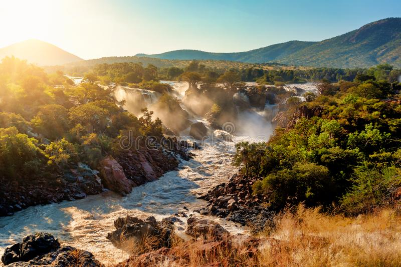 Epupa Falls on the Kunene River in Namibia. Famous Epupa Falls on the Kunene River in Northern Namibia and Southern Angola border. Sunrise sunlight in water mist stock photo