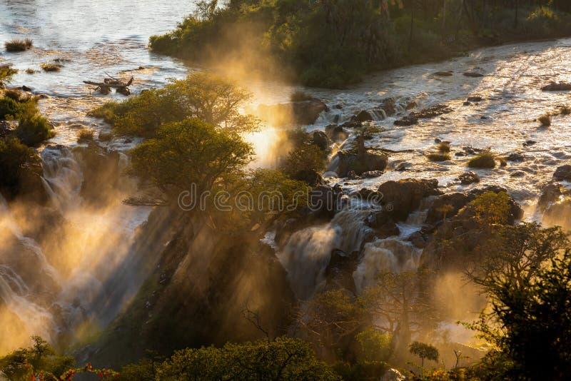 Epupa Falls on the Kunene River in Namibia. Epupa Falls on the Kunene River in Northern Namibia and Southern Angola border. Sunrise sunlight in water mist stock photo
