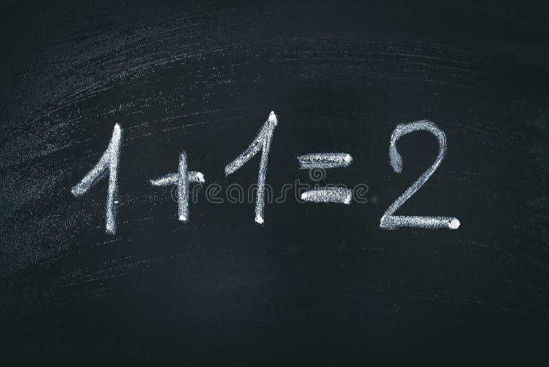 Equação simples da matemática na placa de giz Um mais um iguala dois foto de stock
