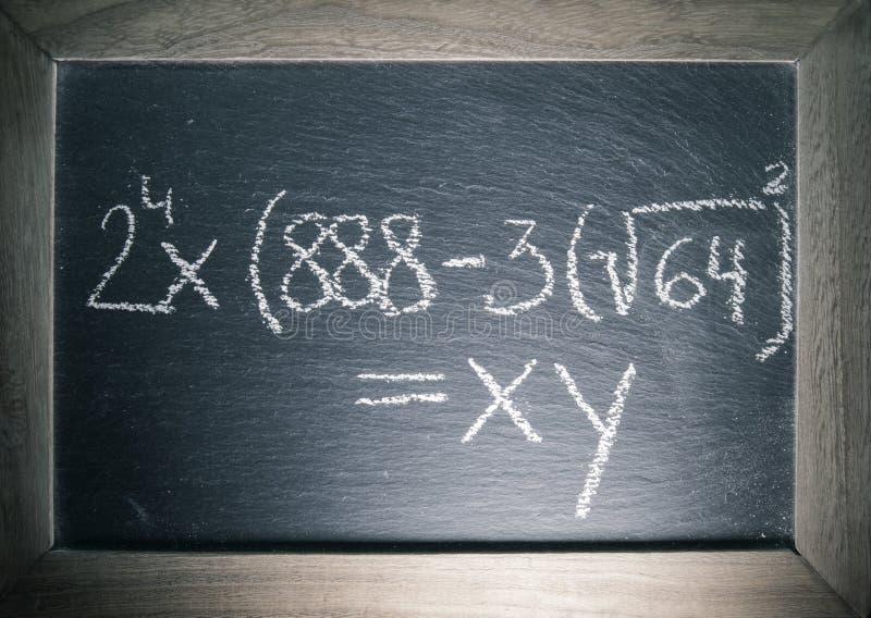 Equações da álgebra da matemática escritas no quadro com quadro de madeira na sala de aula fotos de stock