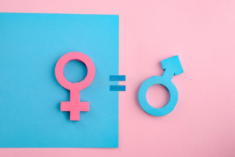 Equality between men and women. 3D paper female and male gender signs on blue and pink background royalty free stock photography