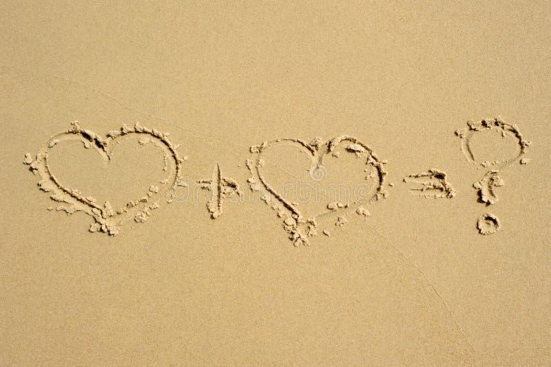 Equazione di amore nella sabbia fotografie stock